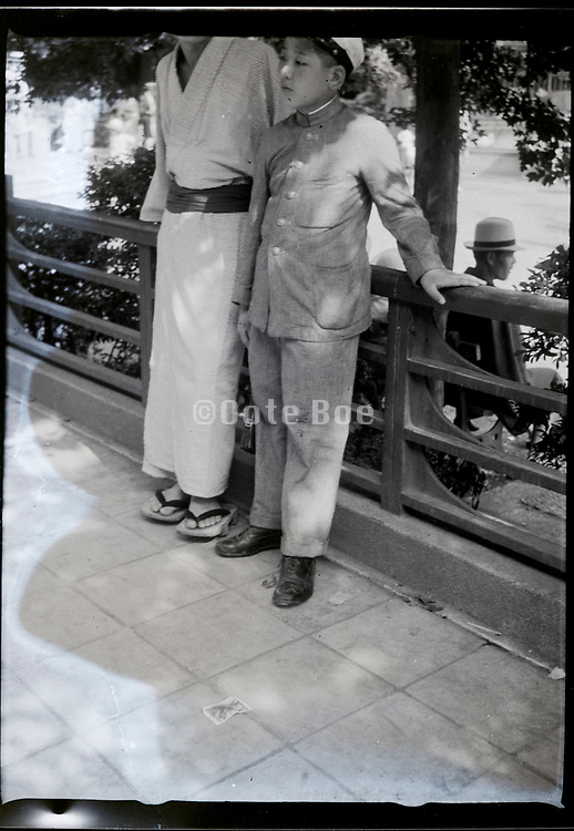 casual image of teo boys resting on a railing outdoors Japan ca 1940s