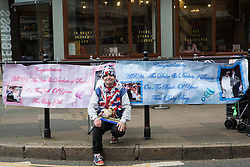 Windsor, UK. 2nd May, 2019. Well-known royal superfan John Loughrey, 64, waits opposite Windsor Castle for the imminent birth of the first child of the Duke and Duchess of Sussex. He has prepared two banners, a pink one for the birth of a daughter and a blue one for the birth of a son.