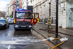 Licensed to London News Pictures. 05/10/2021. London, UK. Firemen at the scene in Knightsbridge, west London where many shops were damaged in severe flooding this morning after torrential rain hit most of London last night. Heavy rainfall has caused severe flooding in London with many roads blocked with flood water and cars trapped. Photo credit: Alex Lentati/LNP
