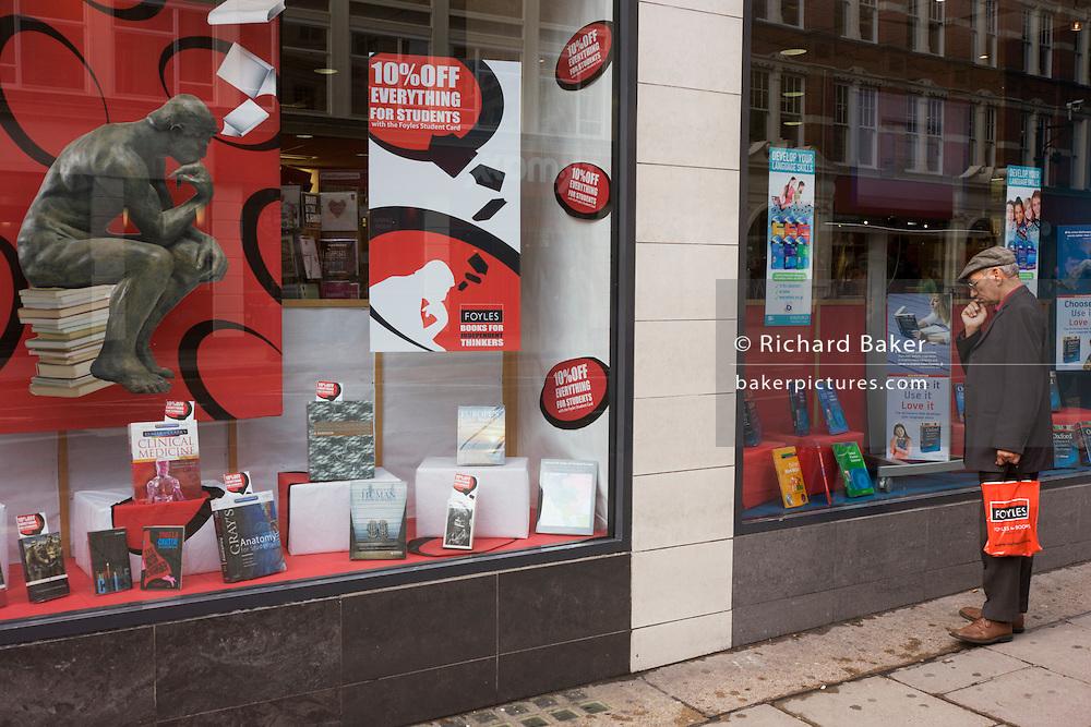 Near Rodin's Thinker poster, a Foyles bookshop customer window shops outside the shop in London, Charing Cross Road.