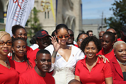 Rihanna poses with volunteers at the 'Man Aware' event held by the Barbados National HIV/AIDS Commission in Bridgetown, Barbados, during his tour of the Caribbean.
