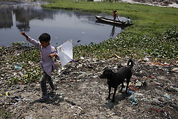 April 25, 2018 - Dhaka, Bangladesh - A boy with a dog on a garbage fly kite near a drain in Dhaka. (Credit Image: © Md. Mehedi Hasan via ZUMA Wire)