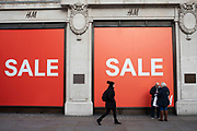 People out shopping on Oxford Street walk past and interact with large scale sale signs in red and white for major high street clothing retail shops on 21st January 2020 in London, England, United Kingdom. Oxford Street is a major road in the West End of London. It is Europes busiest shopping street, with around half a million daily visitors, and has approximately 300 shops.