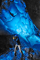 Photographer taking pictures inside an ice cave at Mendenhall Glacier, Juneau, Alaska USA.