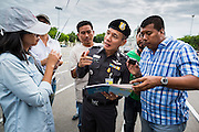 "24 JUNE 2014 - BANGKOK, THAILAND: A Thai police officer (center) talks to a poet (left) while a plain clothes officer (right) photographs her poem after she read it aloud at a meeting of the Monsoon Poets Society in Bangkok. Members of the ""Monsoon Poets Society"" gathered in front of the Anantasamakom Throne Hall Tuesday to pay homage to the People's Party, a Siamese (Thai) group of military and civil officers (which became a political party) that staged a bloodless coup against King Prajadhipok (Rama VII) and changed Thailand (then Siam) from an absolute monarchy to a constitutional monarchy on 24 June 1932. Since the coup against the civilian government on 22 May, the ruling junta has not allowed political gatherings. Although police read the poems, they did not arrest any of the poets or make any effort to break up the gathering.     PHOTO BY JACK KURTZ"