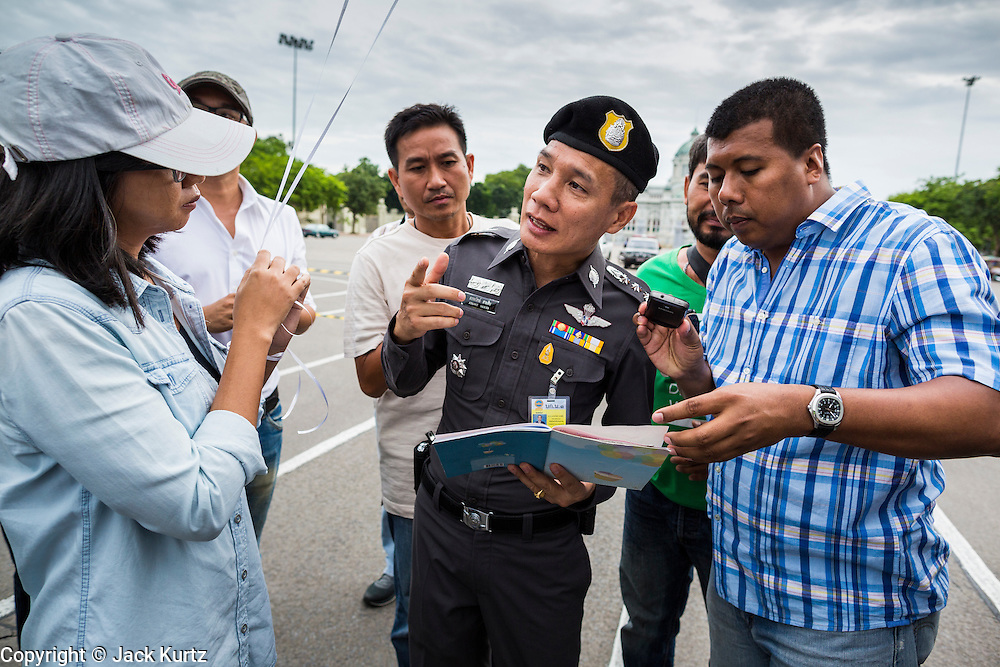 """24 JUNE 2014 - BANGKOK, THAILAND: A Thai police officer (center) talks to a poet (left) while a plain clothes officer (right) photographs her poem after she read it aloud at a meeting of the Monsoon Poets Society in Bangkok. Members of the """"Monsoon Poets Society"""" gathered in front of the Anantasamakom Throne Hall Tuesday to pay homage to the People's Party, a Siamese (Thai) group of military and civil officers (which became a political party) that staged a bloodless coup against King Prajadhipok (Rama VII) and changed Thailand (then Siam) from an absolute monarchy to a constitutional monarchy on 24 June 1932. Since the coup against the civilian government on 22 May, the ruling junta has not allowed political gatherings. Although police read the poems, they did not arrest any of the poets or make any effort to break up the gathering.     PHOTO BY JACK KURTZ"""