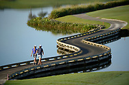 Paige Moffat, left, of Avon Park, Fla., and Christina Miller, of Bradenton, Fla., walk across a pond to the 10th fairway after teeing off during the 2014 U.S. Women's Open Sectional Qualifying at Quail Valley Golf Club in Vero Beach, Fla. on Friday, May 30, 2014. (Copyright USGA/AFLO)