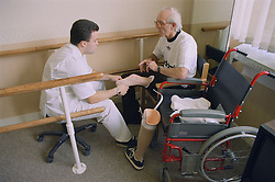 Prosthetist with patient in mobility centre; fitting belowknee (transtibial) prosthesis,
