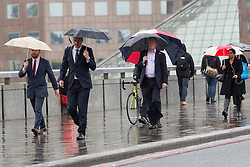 © Licensed to London News Pictures. 04/05/2014. London, UK. Commuters with umbrellas cross London Bridge in the rain this morning. Photo credit : Vickie Flores/LNP