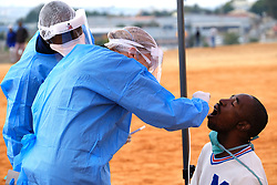 ALEXANDRA SOUTH AFRICA - APRIL 25: Health workers conduct swabs with community member Mr Mashaba. During intensified testing and screening on Freedom Day, screening and testing includes people over over 60, flu-like symptoms, comorbid conditions, like diabetes, asthma, hypertencsion, HIV and tuberculosis on April 25, 2020 in Alexandra South Africa. Under pressure from a global pandemic. President Ramaphosa declared a 21 day national lockdown extended by another two weeks, mobilising goverment structures accross the nation to combat the rapidly spreading COVID-19 virus - the lockdown requires businesses to close and the public to stay at home during this period, unless part of approved essential services. (Photo by Dino Lloyd)