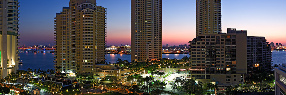 Panoramic view of residential condominium buildings on Miami's Brickell Key (Claughton Island) with the dawn sky, Port of Miami and Miami Beach in the background. WATERMARKS WILL NOT APPEAR ON PRINTS OR LICENSED IMAGES.