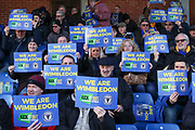 AFC Wimbledon fans with Kick it out signs at ref whistle during the EFL Sky Bet League 1 match between AFC Wimbledon and Peterborough United at the Cherry Red Records Stadium, Kingston, England on 18 January 2020.