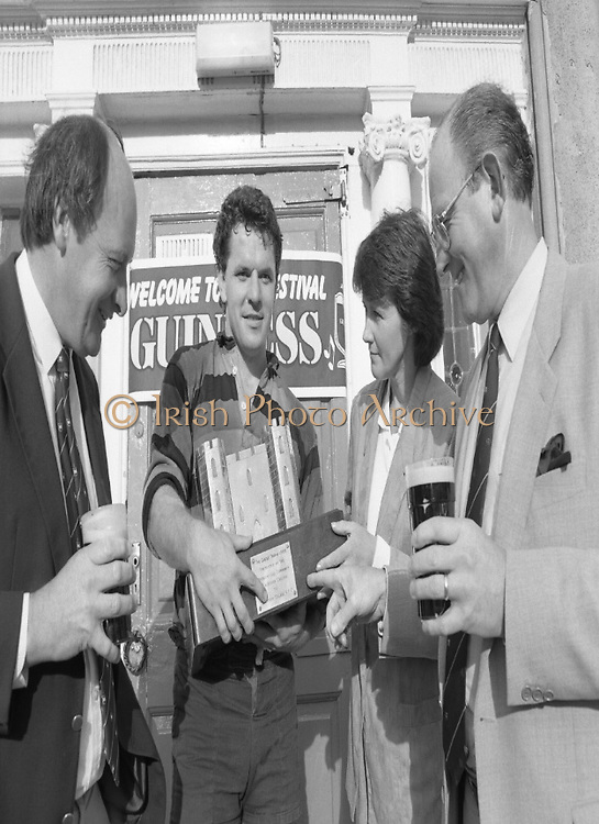 "Guinness Festival of Champions (Rugby).1986..06.09.1986..09.06.1986..6th September 1986..At Guinness,St James' Gate on 1/9/86 it was announced that a Festival of Champions (Rugby), would be held at Stradbrook,Dublin. The event was launched by Irish International Coach,Mr Mick Doyle,Mr Andrew Butler,President,Blackrock RFC,Mr Michael Dunne,Regional Sales Manager,Guinness Group Sales and Mr Fergus Slattery,Irish international...Photograph  shows Mrs Laura Butler,wife of Mr Andy Butler (far left),President,Blackrock College RFC presenting the ""Castle Trophy"" to winning captain Mr Willie Burns. Mr Michael Dunne,Regional Manager,Guinness Group Sales completes the picture..Mr Burns captained Lansdowne RFC to victory in the 'Guinness Blackrock Festival Of Champions'."