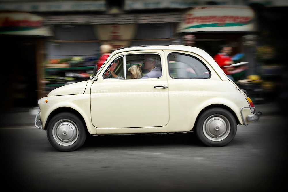 A man driving a Fiat 500 in Sorrento, Italy.