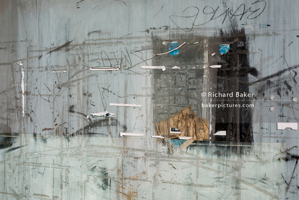 A detail of scratches and the marks of torn down posters in the window of a former shop premises now out of business, on 7th November 2019, in Surbiton, London, England