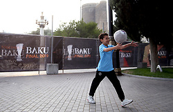 A Local kid play football infant of the Maiden Tower in Baku, Azerbaijan.