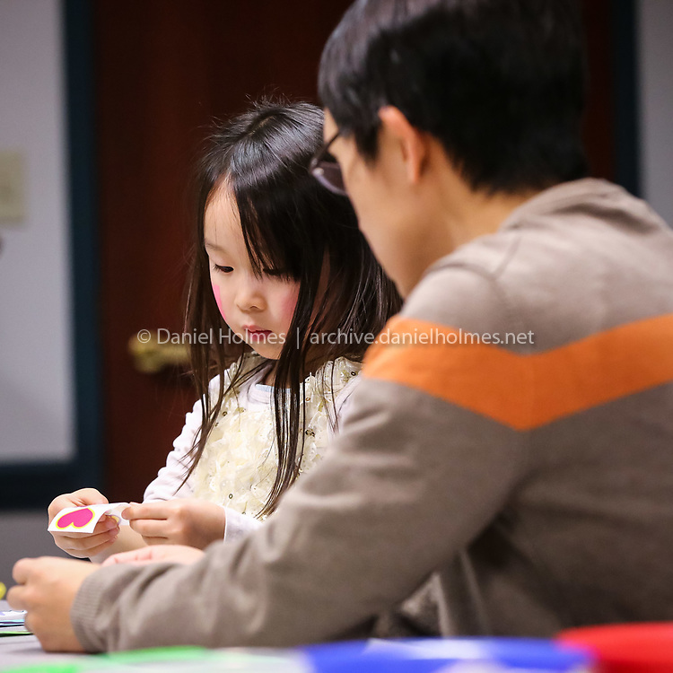 (12/31/15, NATICK, MA) Annabel Chen, 5, of Natick, and her dad Wenjie, work on a craft during the annual Family New Year's Eve Party at the Morse Institute Library in Natick on Thursday. Daily News and Wicked Local Photo/Dan Holmes
