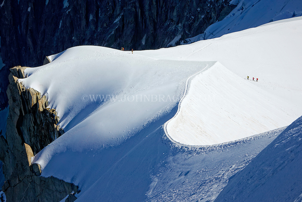 A trio of hikers walking across the French Alps - Chamonix, France.