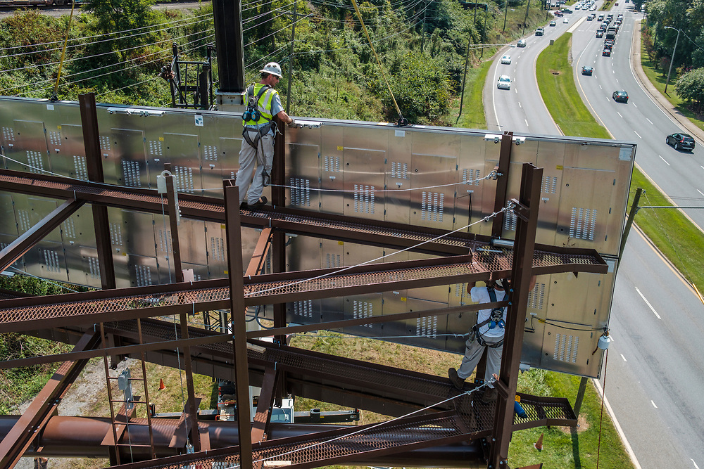 Rick Handy, on top, and Brian Modica, at right, technicians from Lamar Advertising install a digital billboard structure along Wards Road in Lynchburg, VA Wednesday, August 29, 2018. U.S. companies are investing in re-training efforts to fill a slew of open positions as a tight labor market and changing job requirements makes it hard to find qualified staffers.<br /> CREDIT: Justin Ide for The Wall Street Journal<br /> RETRAIN