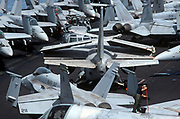 Up on the top deck, a sailor cleans critical wing and flight surfaces from of a parked S-3 Viking on the deck of US Navy aircraft carrier USS Harry S Truman during its deployment patrol of the no-fly zone at an unknown location in the Persian Gulf, on 8th May 2000, in the Persian Gulf. The Truman is the largest and newest of the US Navy's fleet of new generation carriers, a 97,000 ton floating city with a crew of 5,137, 650 are women. (Photo by Richard Baker / In Pictures via Getty Images)
