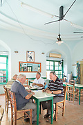 Senior men sitting by table and playing cards, Mytilini, Lesbos, Greece