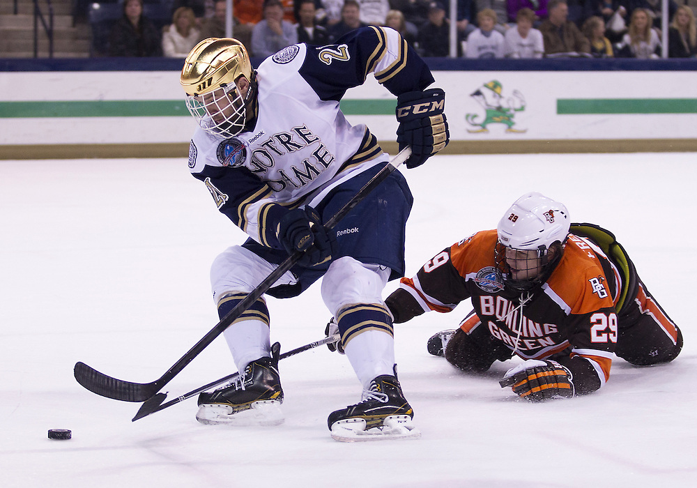 March 15, 2013:  Notre Dame right wing Bryan Rust (21) skates with the puck as Bowling Green defenseman Ralfs Freibergs (29) defends during NCAA Hockey game action between the Notre Dame Fighting Irish and the Bowling Green Falcons at Compton Family Ice Arena in South Bend, Indiana.  Notre Dame defeated Bowling Green 1-0 in overtime.