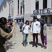 Japanese baseball fans take photographs as they arrive at Yankee Stadium on game day to see Masahiro Tanaka, New York Yankees, pitching during the New York Yankees Vs Tampa Bay Rays, Major League Baseball game at Yankee Stadium, The Bronx, New York. 3rd May 2014. Photo Tim Clayton