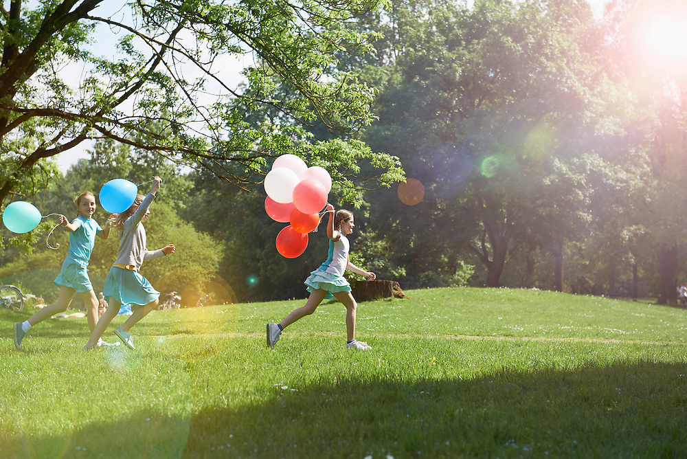 Girls running in park with balloons, Munich, Bavaria, Germany