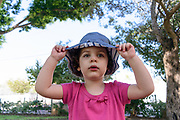 Toddler with hat of head plays outdoors