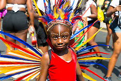A little performer smiles for the camera on Ladbroke Grove as day one, Children's Day, of the Notting Hill Carnival gets underway in London. London, August 25 2019.