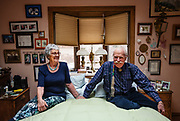 """Mary Kay and John Murphy share a moment in their bedroom at their home of 49 years in Colorado Springs, Colorado. When John was diagnosed with cancer eight and a half years ago, he was told he had mere months to live. But thanks to a then experimental drug, he's been able to continue living his life. He now enjoys riding his e-bike and spending time with his family. When asked where the two spent the most time together in their home, John eagerly responded, """"The bedroom!"""" John then went on to tell a story of the time he convinced Mary Kay to go to a clothing optional hot spring, but they unknowingly went on a day when clothing was required. While laughing, he reminisces about the church group that was also visiting and were absolutely appalled with the couple's nudity."""