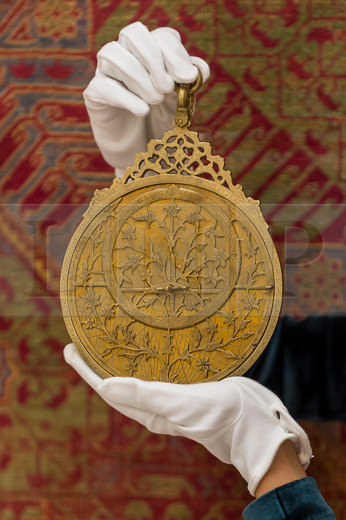 """© Licensed to London News Pictures. 23/10/2020. LONDON, UK. A staff member presents """"A Highly Important Royal Mughal Planispheric Astrolabe, Signed By Diya Al-Din Ibn Muhammad Qa'im"""", India, Lahore, Dated 1068 AH (1657 AD), (Estimate GBP200,000-300,000), at Sotheby's, New Bond Street during the preview of their auction of Treasures from the Islamic World on October 27.  Photo credit: Stephen Chung/LNP"""