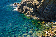 Rocky coastline and blue water, Riomaggiore, Cinque Terre, Liguria, Italy