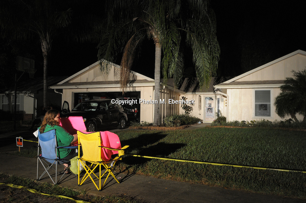 A protester holds a sign while sitting in a chair in front of the home of Casey Anthony in Orlando, Fla., Sunday, Sept. 14, 2008.  Casey Anthony, mother of missing three-year-old Caylee Anthony, is confined to her home while out on bond for charges relating to her missing child.