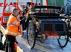 A car taking part in the Bonhams London to Brighton Veteran Car Run is unloaded from a recovery lorry in Crawley, Sussex, after breaking down.