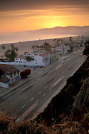 Sunset over PCH Pacific Coast Highway road and mountains along sand beach at Santa Monica, Los Angeles, California
