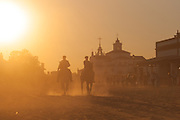 Two riders at sunset, waiting the moment to see the Virgin, the RocÌo Hermitage in the background.