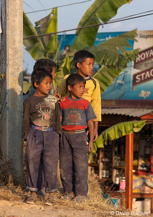 Four Nepalese boys standing at the opposite side of the bus station in Dhulikhel.