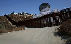 September 7, 2017 - San Diego, California, U.S. - French street artist JR constructed a towering portrait of Kikito, a one-year-old Mexican boy living in Tecate, Mexico next to the border wall. The unveiling came a day after U.S. Attorney General Jeff Sessions announced the Trump Administration's plans to phase out the DACA program, leaving the lives of more than 800,000 undocumented American DACA recipients in limbo. The artist, known as 'French Banksy,' creates large-scale portraits as social commentary. Kikito, about 30-feet tall, is pasted onto a scaffolding about three miles east of the Tecate port of entry. The real Kikito's name is David Enrique, according to Instagram posts by artists. (Credit Image: © Peggy Peattie via ZUMA Wire)