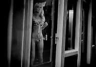 Sex worker in her street front glass booth open to passersby, where she seeks to attract mostly male clientele on a public alleyway in Amsterdam's red light district.  Although prostitution is legal in the Netherlands, young men of Eastern European origin stand guard at the ends of alleyways carefully watching the activities of the young women.  Although the nationality of this particular young woman is not known, many of the sex workers in Amsterdam and the Netherlands are from Eastern Europe.