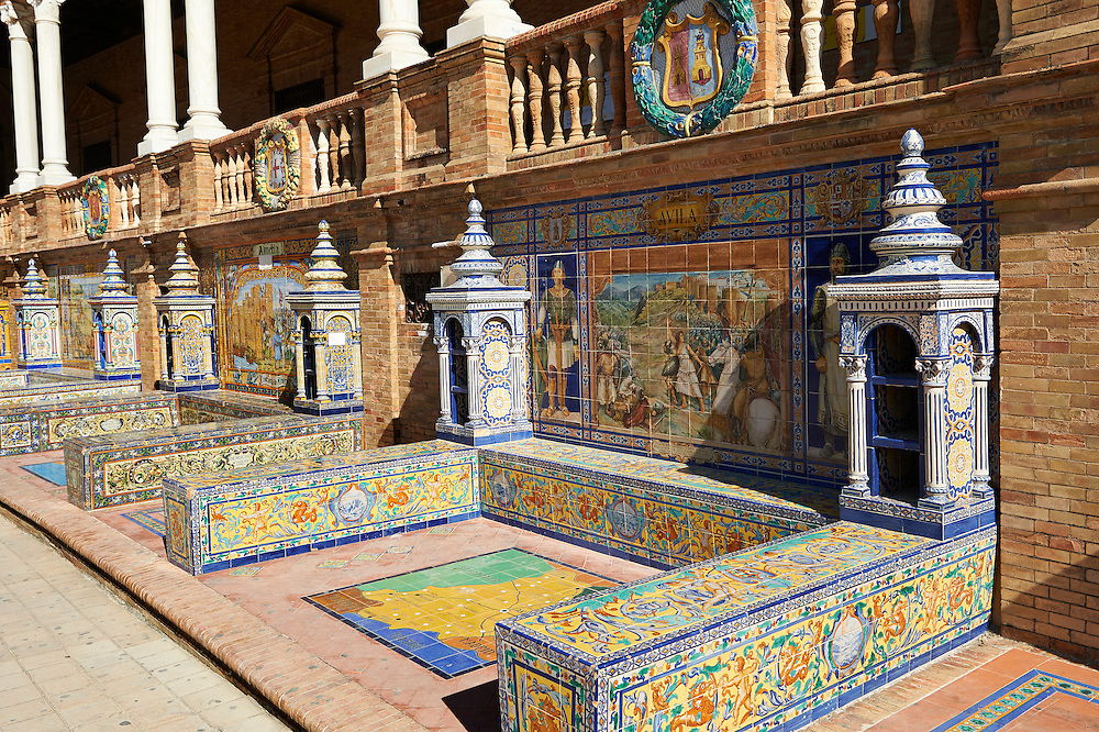 The Avilla alcove along the walls of the Plaza de Espana in Seville built in 1928 for the Ibero-American Exposition of 1929, Seville Spain . The Royal Alcázars of Seville (al-Qasr al-Muriq ) or Alcázar of Seville, is a royal palace in Seville, Spain. It was built by Castilian Christians on the site of an Abbadid Muslim alcazar, or residential fortress.The fortress was destroyed after the Christian conquest of Seville The palace is a preeminent example of Mudéjar architecture in the Iberian Peninsula but features Gothic, Renaissance and Romanesque design elements from previous stages of construction. The upper storeys of the Alcázar are still occupied by the royal family when they are in Seville. <br /> <br /> Visit our SPAIN HISTORIC PLACES PHOTO COLLECTIONS for more photos to download or buy as wall art prints https://funkystock.photoshelter.com/gallery-collection/Pictures-Images-of-Spain-Spanish-Historical-Archaeology-Sites-Museum-Antiquities/C0000EUVhLC3Nbgw <br /> .<br /> Visit our MEDIEVAL PHOTO COLLECTIONS for more   photos  to download or buy as prints https://funkystock.photoshelter.com/gallery-collection/Medieval-Middle-Ages-Historic-Places-Arcaeological-Sites-Pictures-Images-of/C0000B5ZA54_WD0s