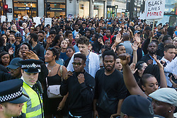 London, July 8th 2016. Hundreds gather on London's Southbank before marching through the streets of London to Parliament Square, Downing Street and the BBC, in a Black Lives Matter protest in solidarity with Americans following the shooting dead of two black men, Philando Castile in Minnesota and Alton Sterling in Louisiana by police in the US. PICTURED: The crowd brings traffic to a stop as they regroup in Oxford Circus.