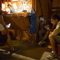 Illegal migrants charge their mobile phones at a transit zone at the railway station in Szeged (about 173 km South of capital city Budapest), Hungary on September 01, 2015. ATTILA VOLGYI