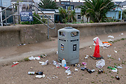 The morning after Saturday night crowds of young peoples' nightlife beach parties, their litter and rubbish from the night before is trewn across the coastal paths and shingle along the sea wall, on 19th July 2020, in Whitstable, Kent, England.  A group of local volunteers and council cleaner will soon arrive for the regular morning clean-up that has got worse, they say, during the Coronavirus pandemic lockdown and now, the slow easing of health guidelines.