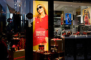 A shop window and poster girl of the high street chain and British export success, beneath a poster girl for Burberry sunglasses they call Eyewear, in a sunlit London street. in a sunlit London street. Burberry Group plc is a British luxury fashion house, manufacturing clothing, fragrance, and fashion accessories.
