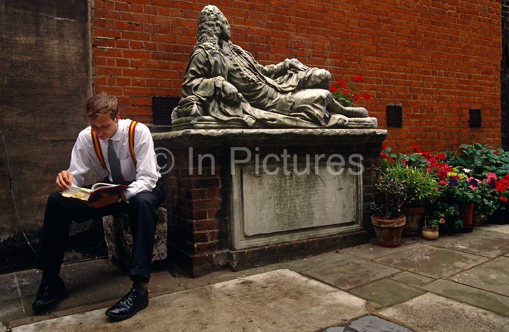 Wearing braces, striped shirt and sitting on a block, a young lawyer studies a legal book during a mid-morning break in the Inner Temple in the historic City of London. The Honourable Society of the Inner Temple is one of the four Inns of Court around the Royal Courts of Justice which may call members to the Bar and so entitle them to practise as barristers. The Temple was occupied in the twelfth century by the Knights Templar, who gave the area its name but was heavily bombed during the Blitz of 1940-1 and the reclining marble memorial to predecessor, John Hiccocks who held the office of Master in Chancery between 1702 and 1723 (d 1726) behind the young law student is marked by the partially-demolished Goldsmiths Chambers on the north side of Temple Church where Hiccocks is buried. An assortment of potted red plants add to an otherwise dark courtyard