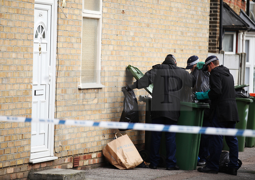 © London News Pictures. 01/11/2013. London, UK. Police search bins near  the scene of the shooting of two shop workers at Show Supermarket in High Street, Plaistow, London. One man in his 50s is in a critical condition and the other in his 40s is in a stable condition in hospital. Photo credit: LNP