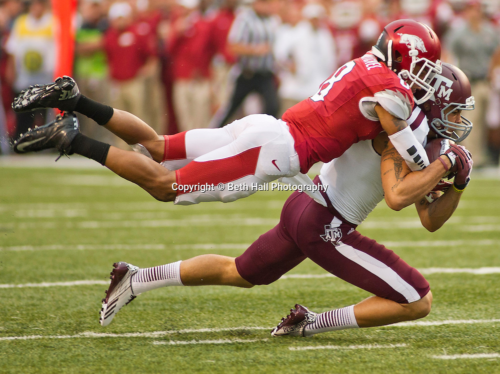 Texas A&M wide receiver Mike Evans (13) is brought down by Arkansas Razorbacks cornerback Tevin Mitchel (8) during an NCAA college football game in Fayetteville, Ark., Saturday, Sept. 28, 2013. Texas A&M defeated Arkansas 45-33. (AP Photo/Beth Hall)