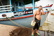 18 JUNE 2013 - YANGON, MYANMAR:   A Burmese crewman on small river freighter bathes with water taken from the Yangon River in Yangon, Myanmar.    PHOTO BY JACK KURTZ