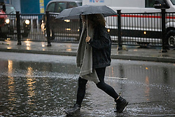 © Licensed to London News Pictures. 14/09/2021. London, UK. A woman walks through deep  surface water on the Euston road in North London during heavy rainfall. Heavy rain is expected to cause flash flooding in parts of the UK. Photo credit: Ben Cawthra/LNP
